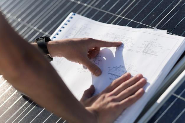 Feche acima da vista na mão que aponta em desenhos técnicos. Foto Premium