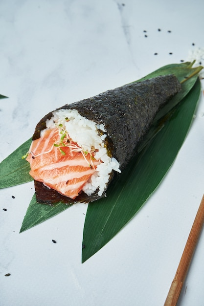 Feche acima da vista no fresco, sushi do temaki do marisco com salmões no branco. Foto Premium