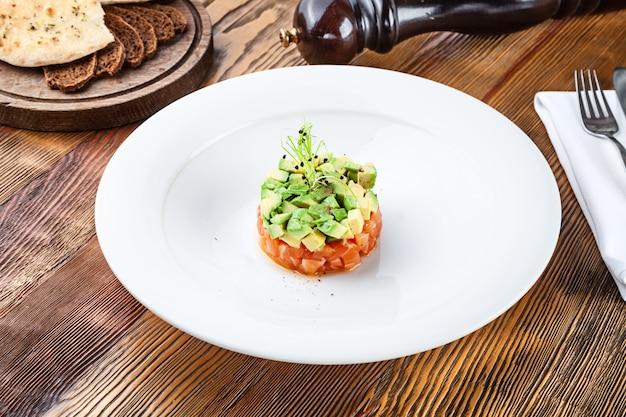 Feche acima da vista no tartare de salmão fresco com abacate e microgreen na placa branca. tartare caseiro em fundo de madeira com espaço de cópia. comida servida para menu ou receita. lanche de cozinha italiana Foto Premium