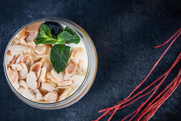 Feche acima da vista no tiramisu saboroso com porca e manga. sobremesa servida em fundo escuro, com espaço de cópia. imagem para menu ou receita. Foto Premium