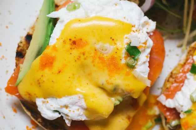 Feche acima da vista superior dos ovos benedict com salmões e abacate, servidos com salada na placa branca. Foto Premium