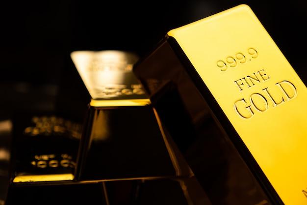 Feche acima das barras de ouro no bacground preto. conceito financeiro Foto Premium