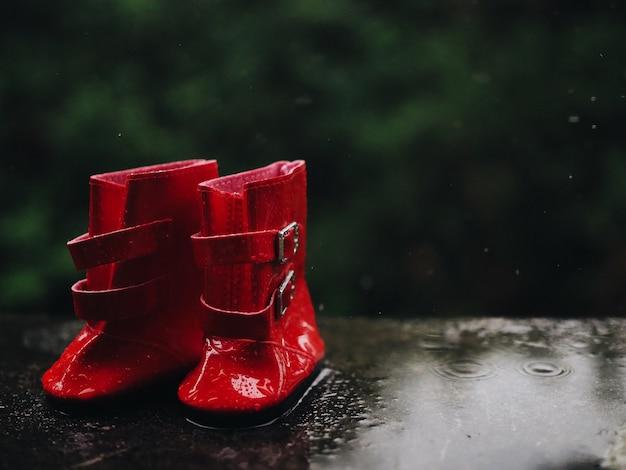 Feche acima das botas vermelhas de borracha no assoalho molhado. Foto Premium