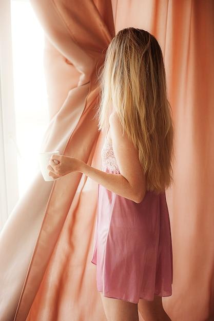 Feche acima das cortinas de janela felizes da abertura da mulher. linda menina está acordada e em pé antes Foto Premium