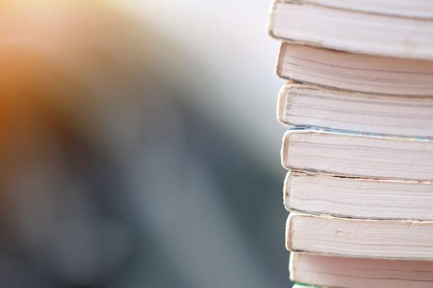 Feche acima das imagens de muitos livros empilhados no fundo borrado. Foto Premium