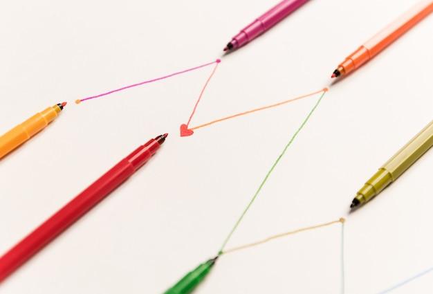 Feche acima das linhas conectadas pintadas com marcadores coloridos no livro branco. linhas para gráficos, horário Foto gratuita