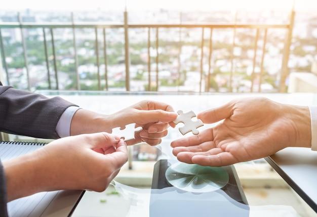 Feche acima das mãos conectar dois quebra-cabeças. conceito de negócio, sucesso e estratégia. Foto Premium