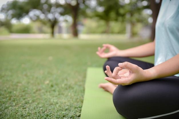 Feche acima das mãos da mulher fazem a ioga ao ar livre no parque. Foto Premium