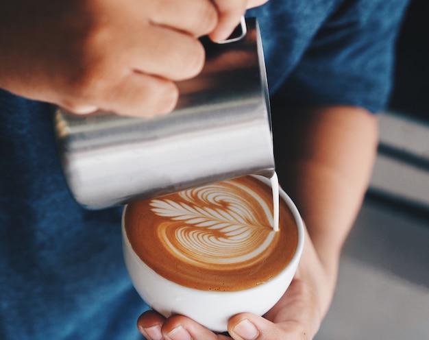 Feche acima das mãos do barista que derramam o leite morno no copo de café para fazer a arte do latte. Foto Premium