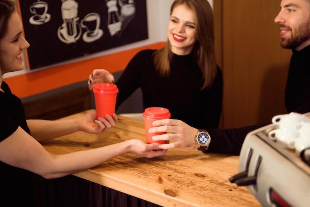 Feche acima das mãos que tomam o copo do café quente do barista na loja dos confeitos. Foto Premium
