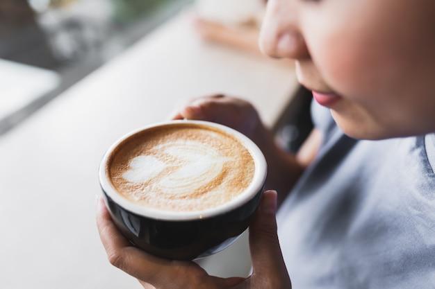 Feche acima das mulheres asiáticas estão bebendo o café do cappuccino no café da manhã Foto Premium
