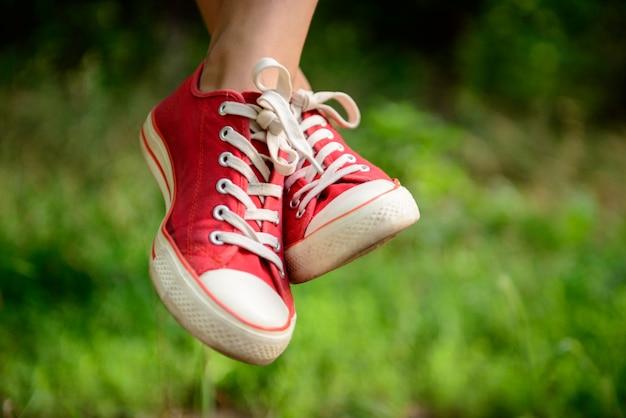 Feche acima das pernas da menina em keds vermelhos na grama. Foto gratuita