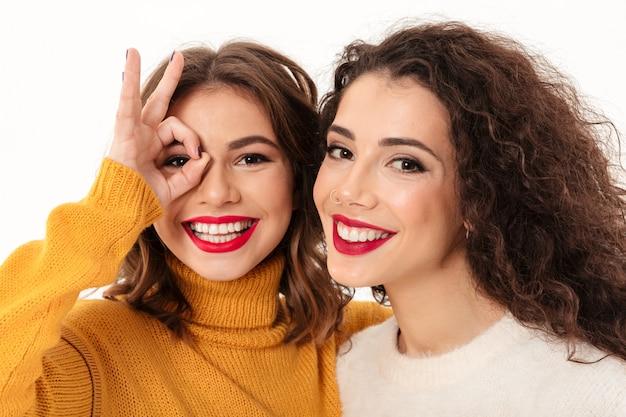 Feche acima de duas meninas felizes em camisolas se divertindo sobre parede branca Foto gratuita