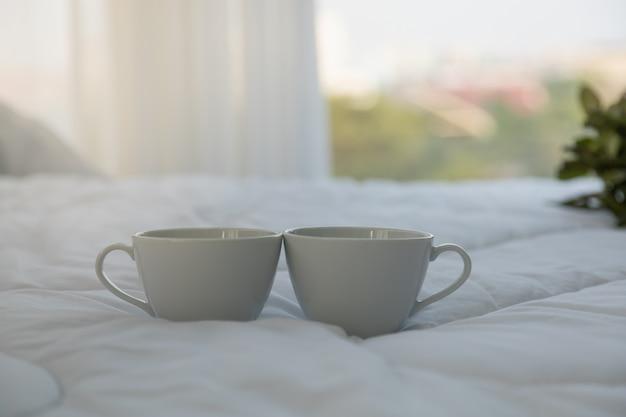Feche acima de duas xícaras de café quentes brancas na cama no quarto com espaço da cópia da manhã. Foto Premium