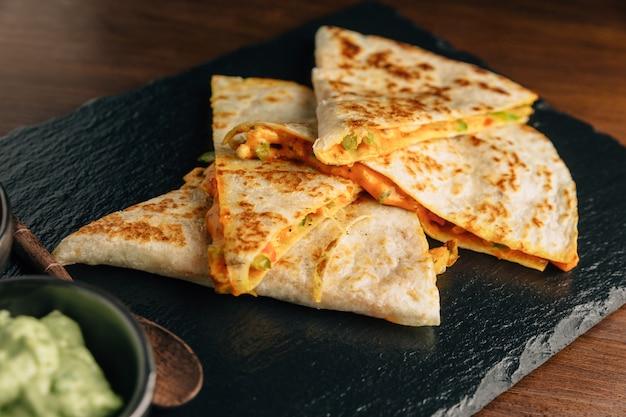 Feche acima de quesadillas cozidos da galinha e do queijo servidos com salsa e guacamole na placa de pedra. Foto Premium