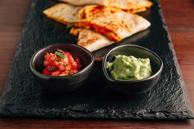 Feche acima de quesadillas cozidos da galinha e do queijo servidos com salsa e guacamole. Foto Premium