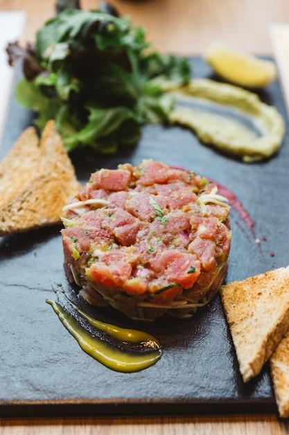 Feche acima de tartare picante do atum de bluefin com molho ácido e picante. servido com torradas e salada na placa de pedra preta. Foto Premium