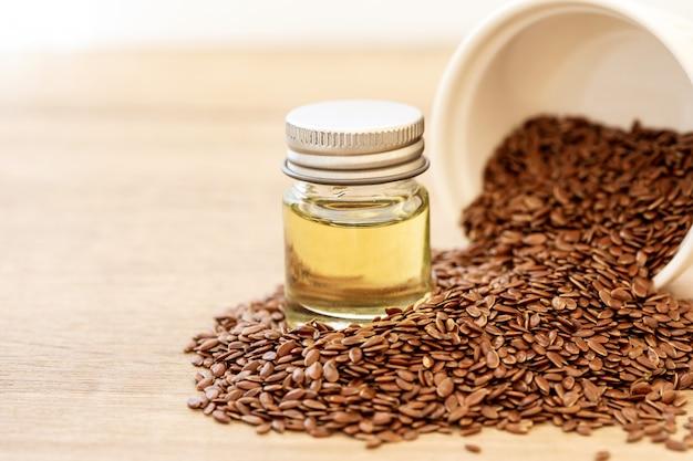 Feche acima de um óleo essencial e de sementes de linhaça na colher de madeira, alimento saudável do coração que superalimento e rico do ômega 3 Foto Premium