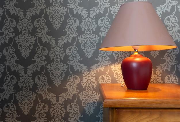 Feche acima de uma cama de madeira com lençóis brancos e uma lâmpada acolhedor, teste padrão do papel de parede design retro. Foto Premium