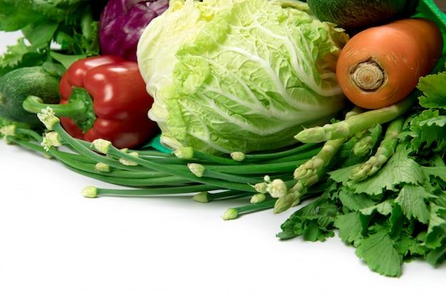 Feche acima de uma sacola verde de vegetais verdes orgânicos misturados no branco Foto Premium