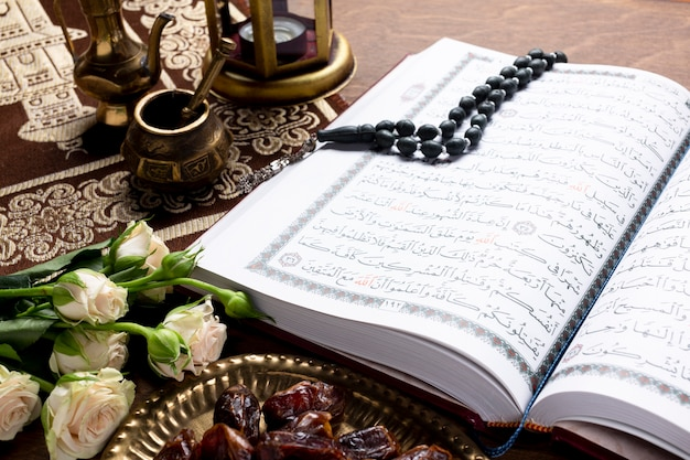 Feche acima do alcorão aberto e itens islâmicos Foto gratuita
