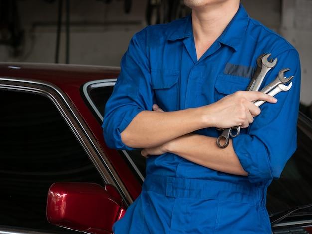 Feche acima do auto mecânico em ferramentas ou de chaves de terra arrendada uniformes na garagem. Foto Premium