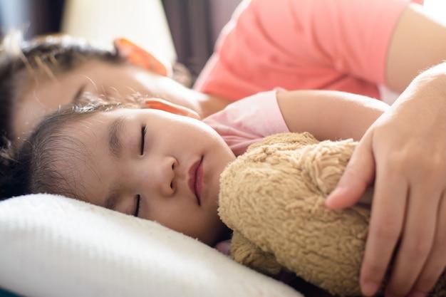 Feche acima do bebê asiático bonito e sua mãe dormindo na cama. vista lateral Foto Premium