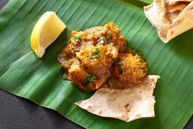 Feche acima do caril e do limão indianos tradicionais da galinha da manteiga servidos com pão do chapati na folha da banana. Foto Premium