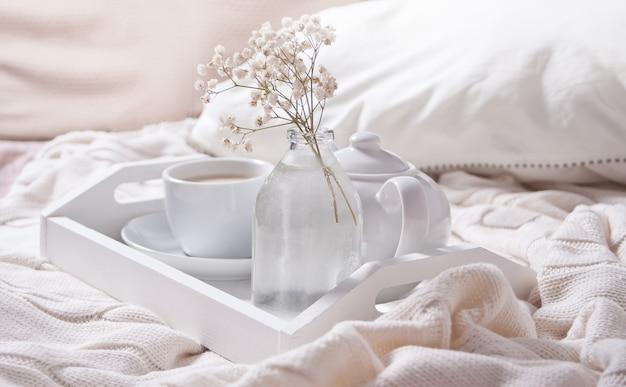 Feche acima do copo do chá, do leite, do bule e do ramalhete das flores brancas na bandeja branca. Foto Premium