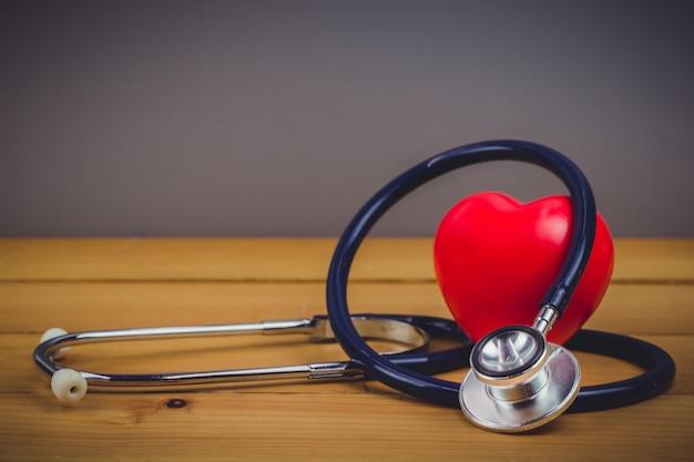 Feche acima do coração vermelho e steythoscope na tabela de madeira velha Foto Premium