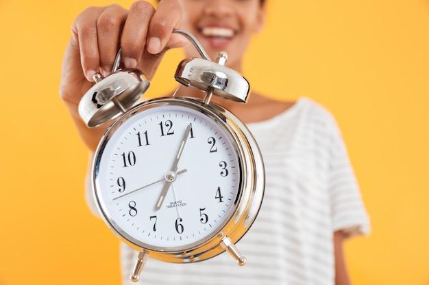 Feche acima do despertador na mão da mulher isolada Foto gratuita