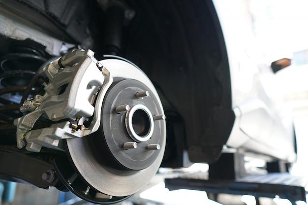 Feche acima do disco do freio do veículo para o reparo. Foto Premium