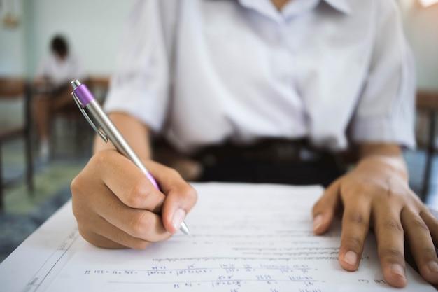 Feche acima do estudante que lê e que escreve o exame com esforço na sala de aula. Foto Premium