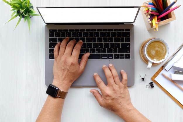 Feche acima do homem que trabalha no portátil ao sentar-se na mesa de madeira branca no escritório moderno. Foto Premium