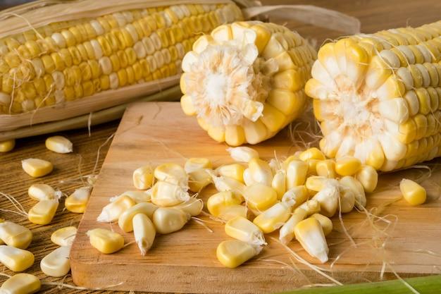 Feche acima do milho doce fresco na tabela de madeira. Foto Premium