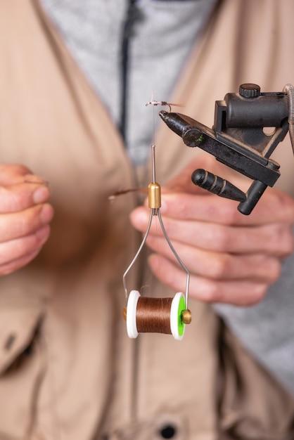 Feche acima do pescador que amarra uma mosca para pescar. Foto Premium