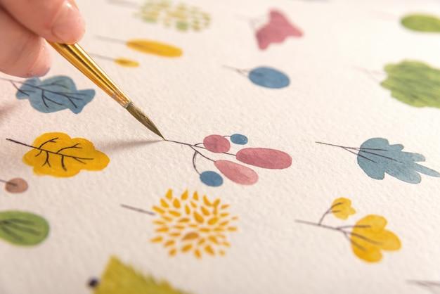 Feche acima do projeto colorido diferente da natureza das flores pintado com pincel e aquarelas no papel Foto gratuita