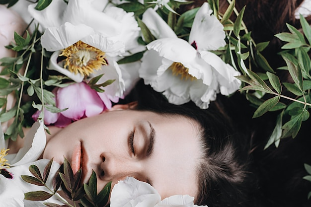 Feche acima do retrato da mulher moreno bonita nas flores brancas e roxas. relaxamento menina caucasiano no parque com peônias fora Foto Premium