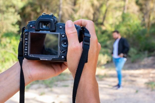 Feche acima do retrato do homem do fotógrafo que toma a imagem com câmara digital. trabalho, conceito de sessão. Foto Premium
