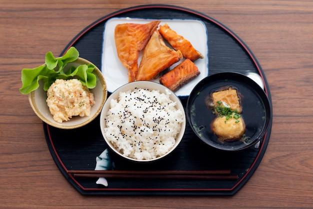 Feche acima do salmão teriyaki de comida japonesa com arroz conjunto servido na mesa de madeira. Foto Premium