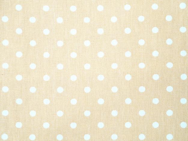 Feche acima do tecido de algodão de creme de superfície com fundo branco do teste padrão de bolinhas. Foto Premium