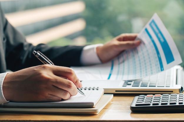 Feche acima do tiro das mãos do homem de negócios com caneta escrevendo notas em um papel e por outro lado, segurando o gráfico de marketing. Foto Premium