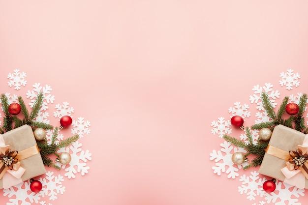 Feche acima do tiro do presente pequeno envolvido com a fita no fundo rosa. fundo de natal. conceito mínimo. Foto Premium
