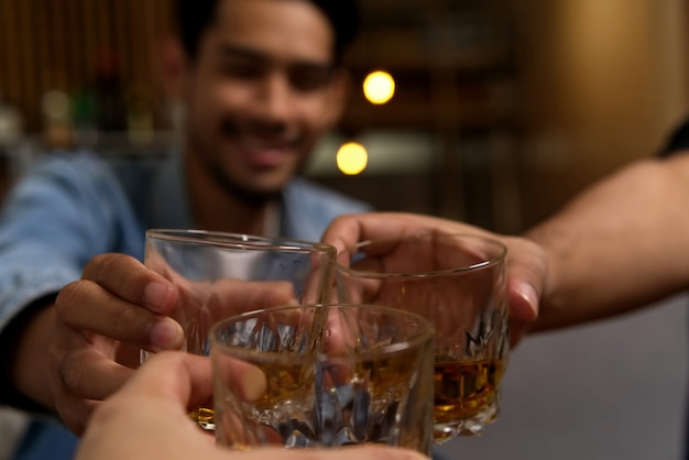 Feche acima do tiro dos vidros que clinking entre o grupo de amigos que bebe o uísque na festa da noite no restaurante. Foto Premium