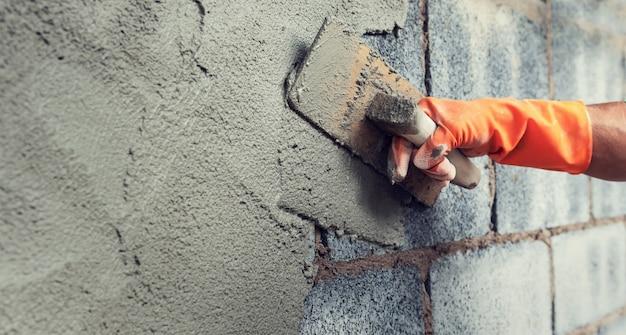 Feche acima do trabalhador de mão que reboca o cimento na parede para construir a casa Foto Premium
