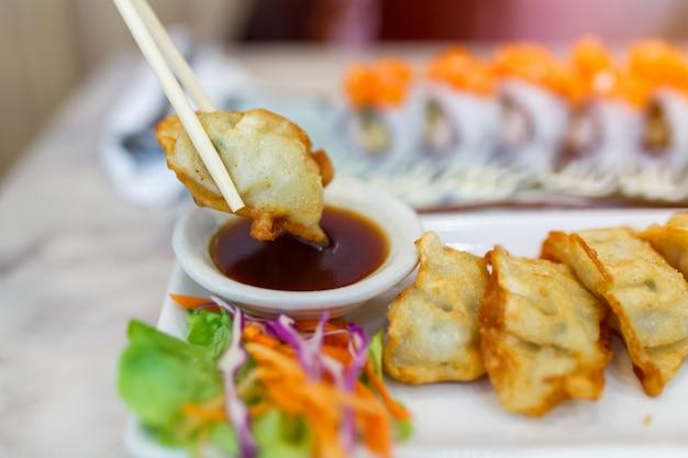 Feche acima dos hashis que apertam as bolinhas de massa do gyoza (gyoza japonês) que sentam-se em uma tabela de madeira rústica no restaurante chinês. Foto Premium