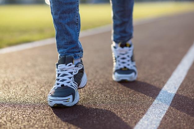Feche acima dos pés da mulher no esporte tênis e calças de ganga na pista de corrida na quadra de esportes ao ar livre. Foto Premium