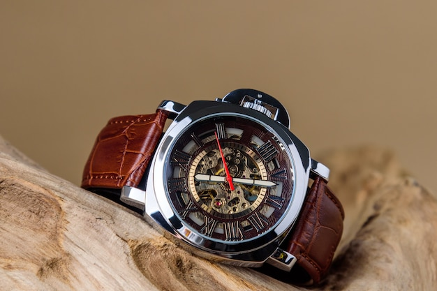 Feche acima dos relógios de pulso luxuosos do homem colocados na madeira no fundo marrom Foto Premium