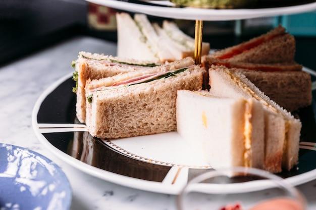 Feche acima dos sanduíches na bandeja cerâmica do serviço de 3 séries para comer com chá quente. Foto Premium