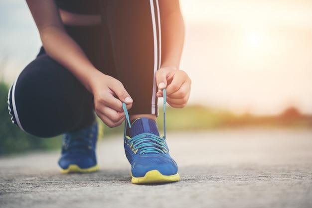 Feche acima dos sapatos feminino corredor amarrando os sapatos para um exercício de jogging Foto gratuita